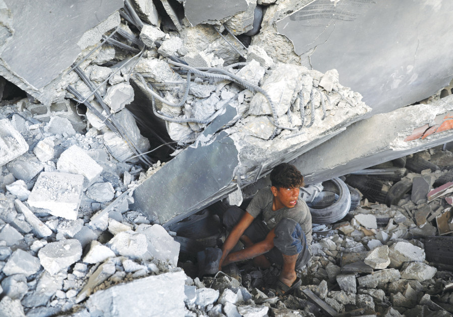 A GAZA CITY resident searches for his belongings under the rubble of a building that was destroyed