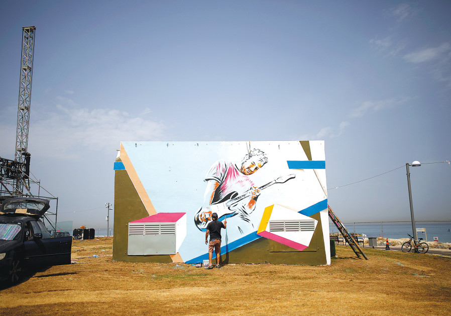 A MAN PAINTS a mural on a structure located close to the Eurovision Village in Tel Aviv