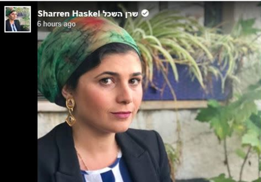 Sharren Haskel puts on a head covering.