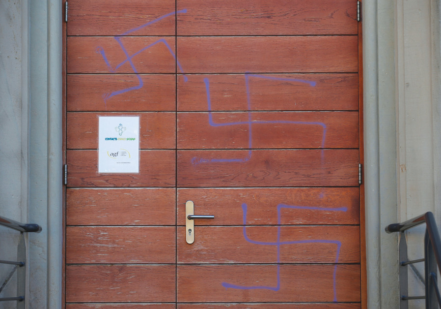 SWASTIKAS ARE SEEN painted on the main door of a former synagogue turned into a cultural center in M