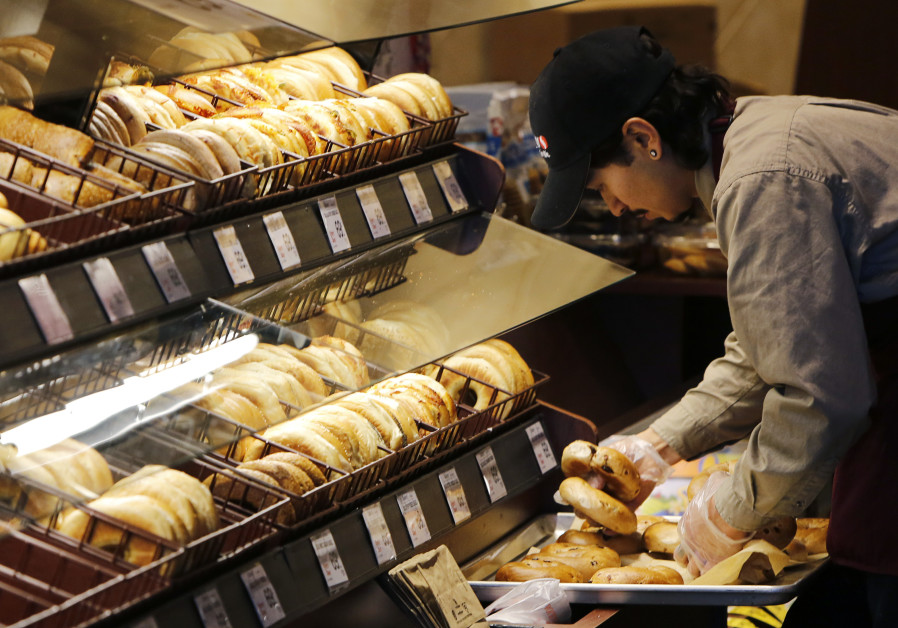 A baker puts out fresh bagels at the store, 2015.