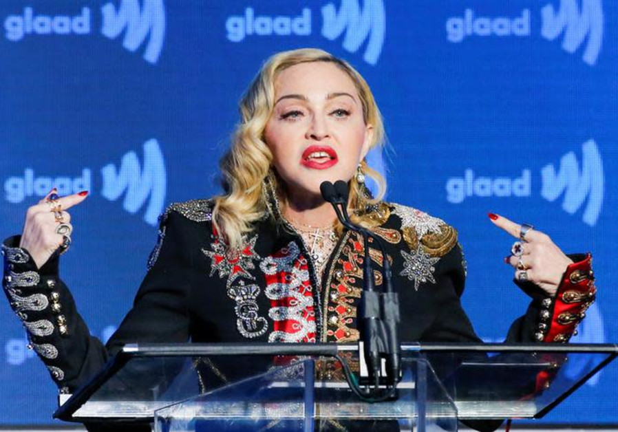 Singer Madonna speaks to guests after receiving the Advocate for Change award