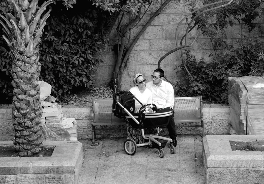 A young Jewish couple relaxing on a public bench in the Jewish Quarter (Eitan Simanor)