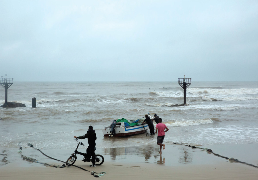 Fishermen help push out a boat during rough waters (credit: TAYLOR RENEE BISSEY)