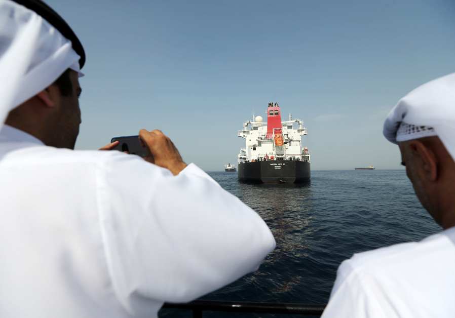 Port officials take a photo of a damaged Andrea Victory ship at the Port of Fujairah, UAE, May 13