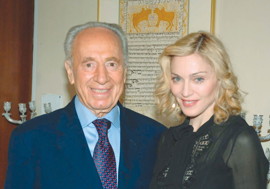 THEN-PRESIDENT Shimon Peres poses with pop singer Madonna during their meeting at the President's Re