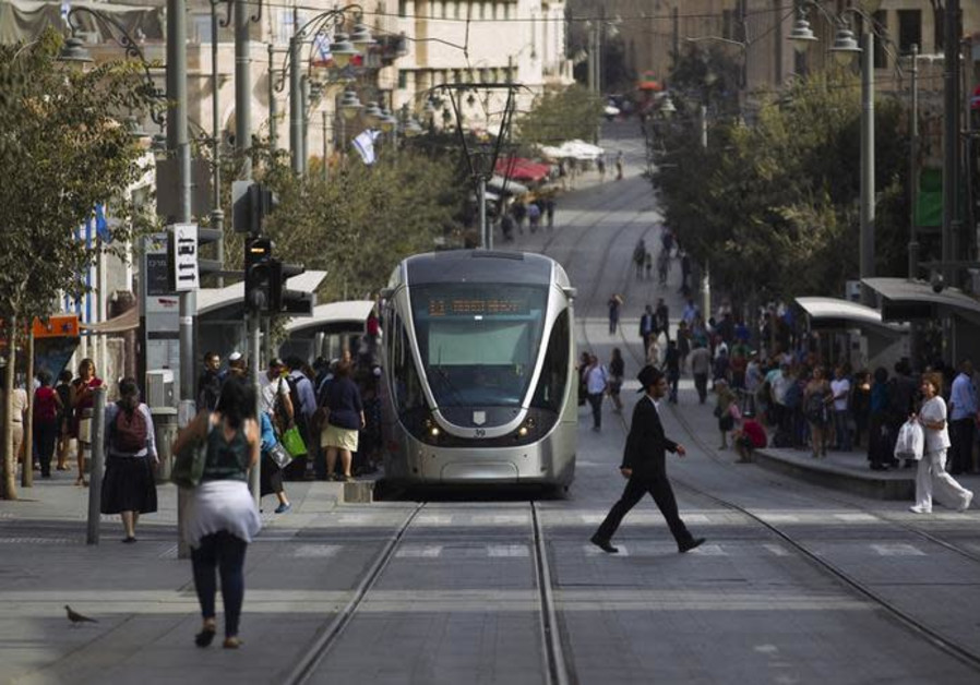 People walk near the light rail in the centre of Jerusalem