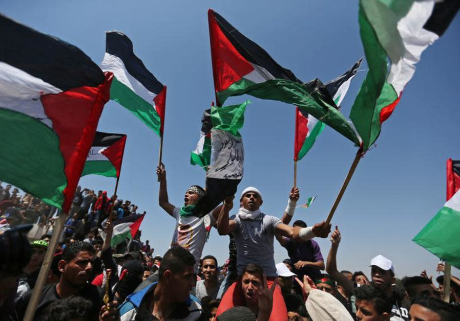 Demonstrators hold Palestinian flags during a protest marking the 71st anniversary of the 'Nakba', o