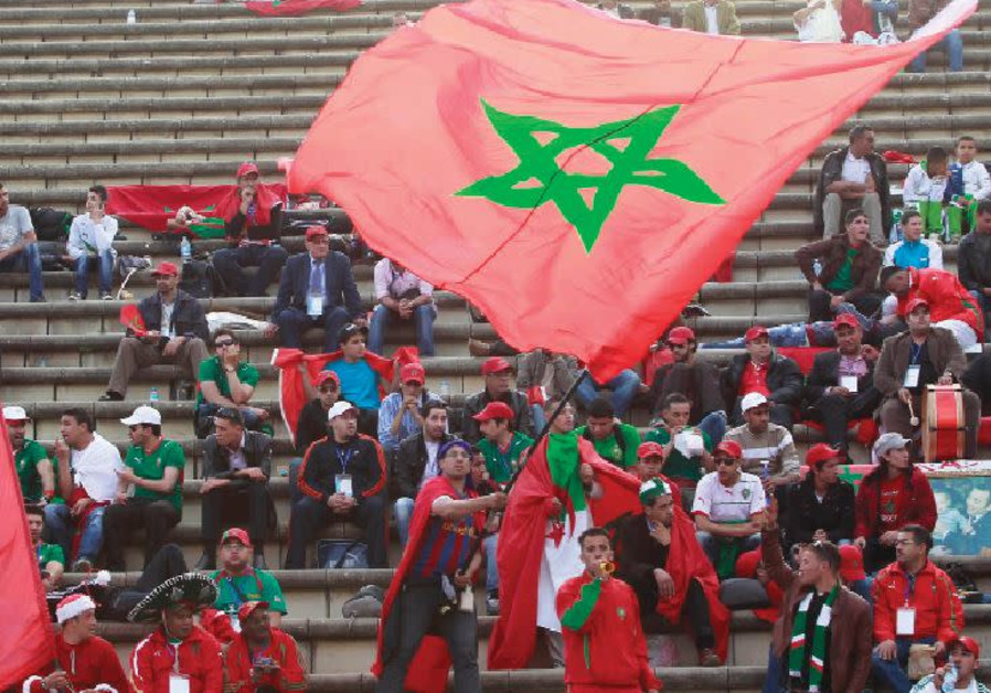 A MOROCCO FAN waves his national flag at a soccer match.