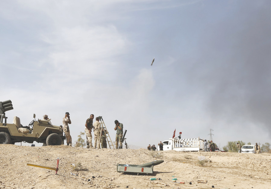 SHI'ITE FIGHTERS launch a mortar round toward Islamic State lines in al-Fatha, northeast of Baiji, i