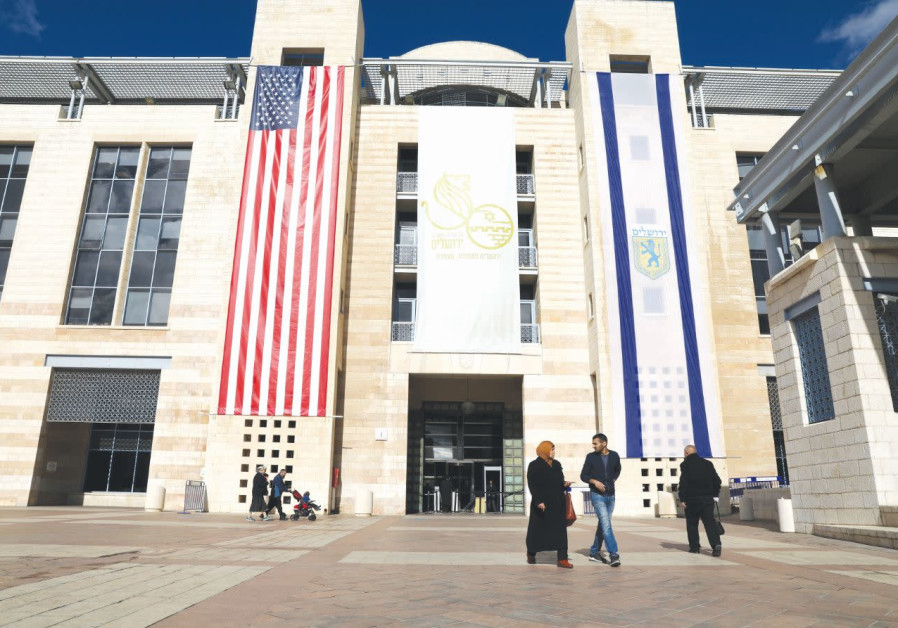PEOPLE WALK at Jerusalem's City Hall as the American and Jerusalem flags hang on the municipality bu