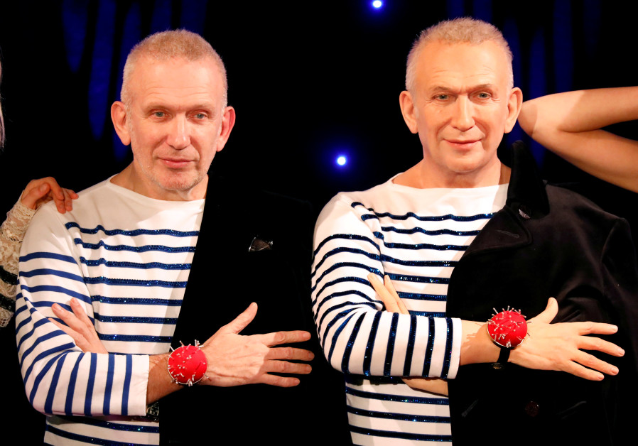 French fashion designer Jean-Paul Gaultier (L) stands next to a sculpted figure of him