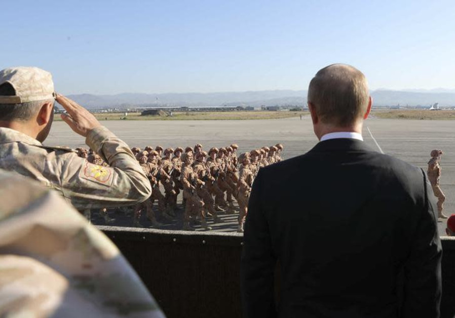 Russian President Vladimir Putin (R) and Defence Minister Sergei Shoigu watch servicemen passing by
