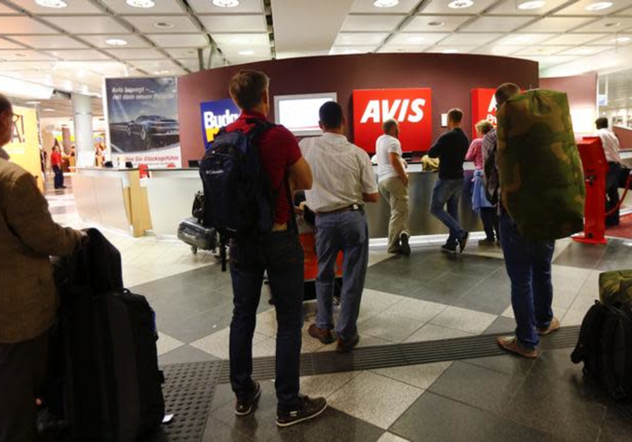 People queue at rental car desks at the international airport in Munich