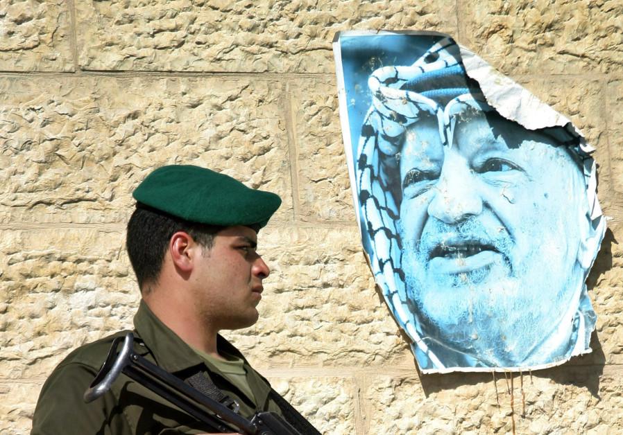 Palestinian policeman guards Palestinian President Abbas' compound in Ramallah