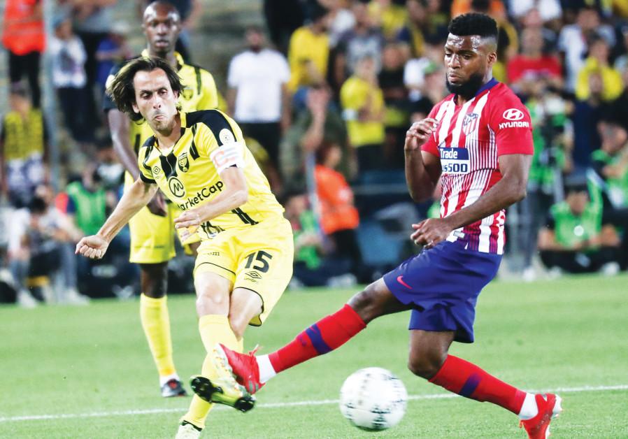 BEITAR JERUSALEM midfielder Yossi Benayoun (left) shoots past Atletico Madrid' Thomas Lemar during l