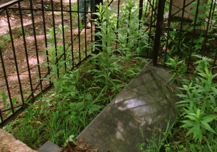 A man looks at a fallen tombstone at Jewish cemetery in Malakhovka, some 25 km east from Moscow