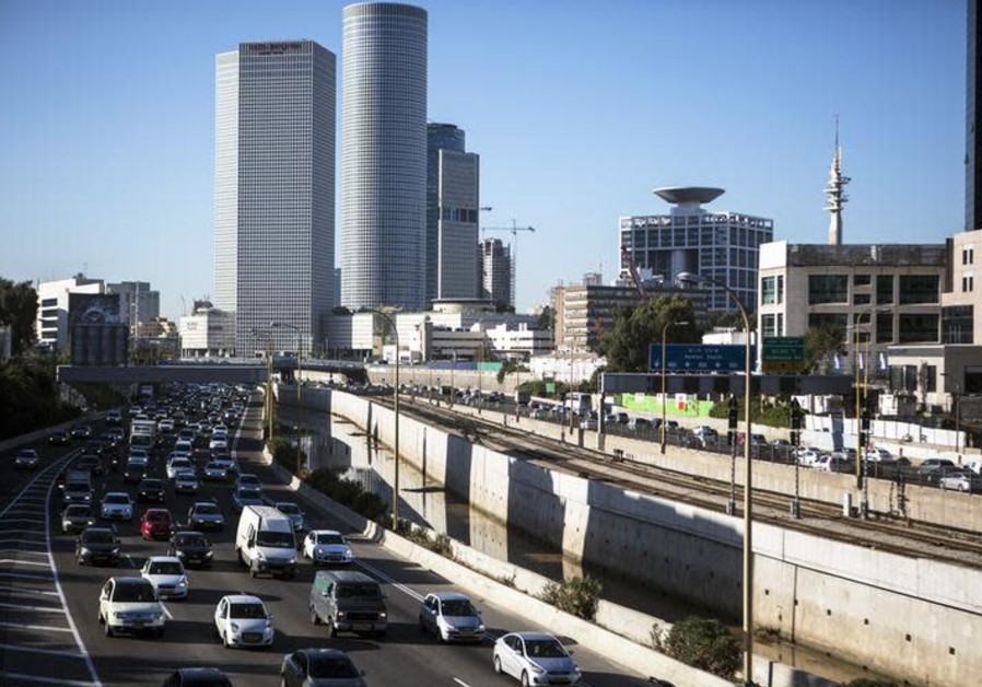Vehicles drive on a highway in the central Israeli city of Tel Aviv