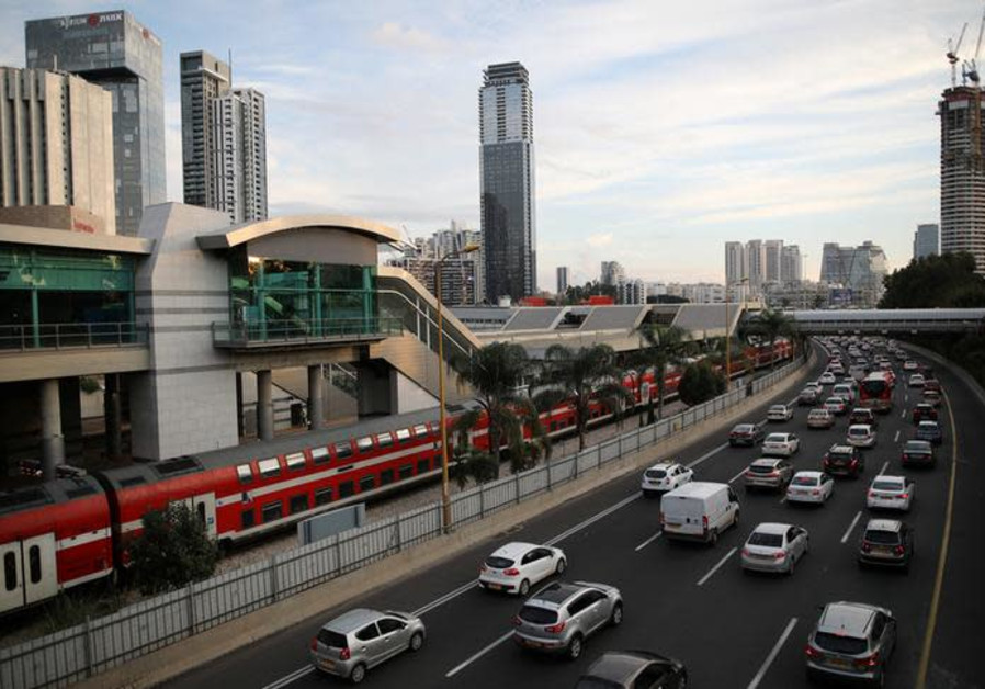 Cars drive on a highway as a train enters a station in Tel Aviv
