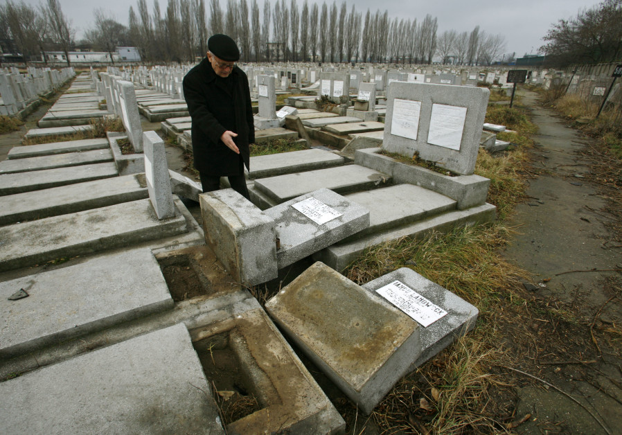 A member of Romania's Jewish community points to devastated graves at a Jewish cemetery in Bucharest