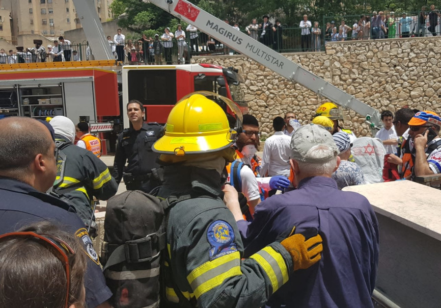 The fire and rescue forces in Tsfat help citizens out of their building which rose up in flames.