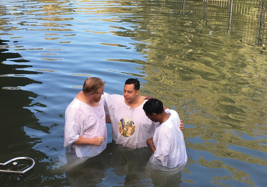 Harrison Manyoma, far right, baptizing a fellow soldier in the Jordan River. (photo credit: Courtesy)