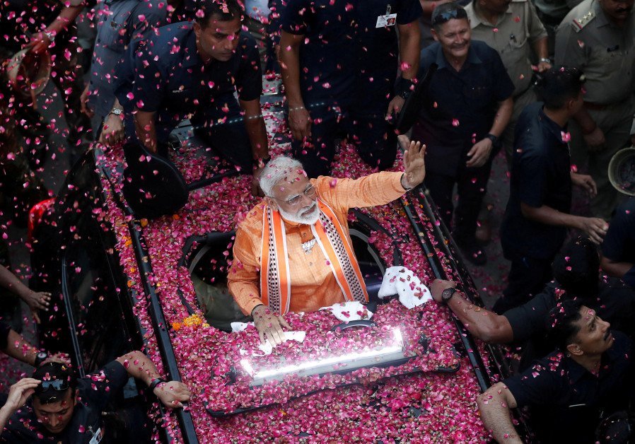 India's Prime Minister Narendra Modi waves towards his supporters during a roadshow in Varanasi, In