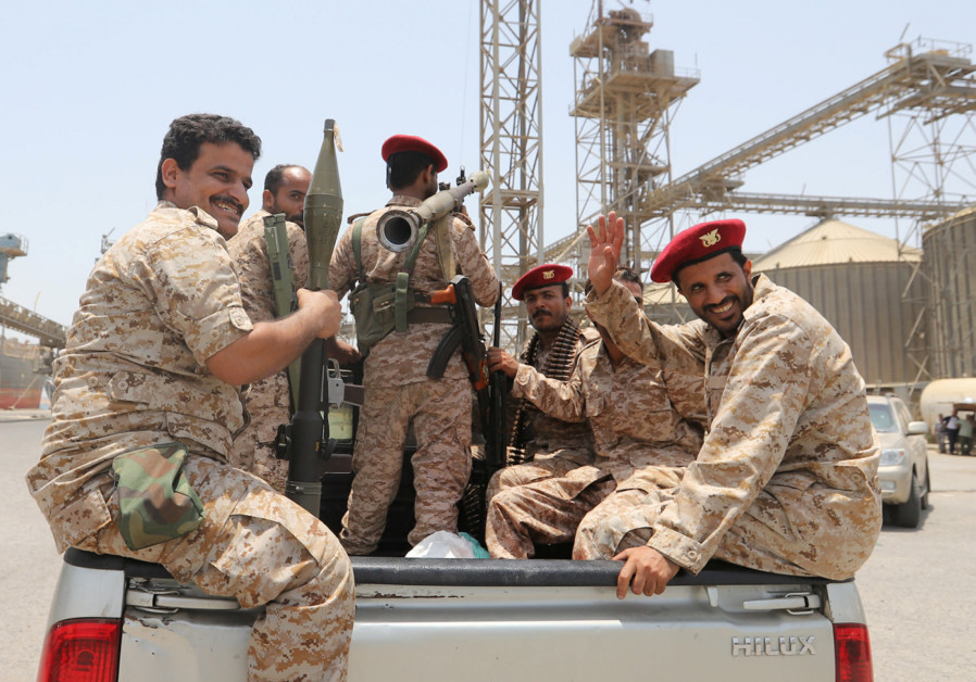 Yemen's Houthi movement forces ride in the back of a vehicle during withdrawal from Saleef port in H