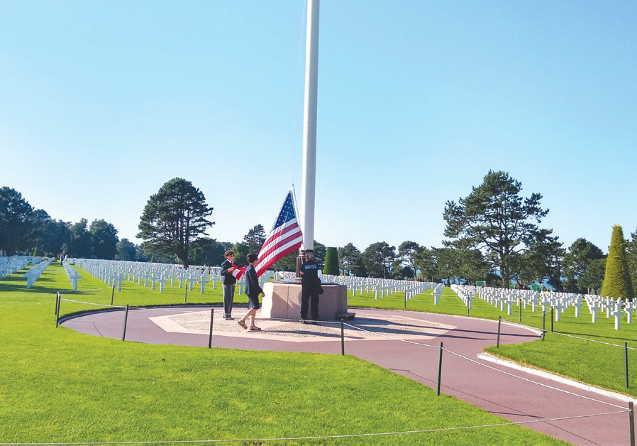 LOWERING THE flag at the American cemetery in Normandy, where 9,387 US servicemen were laid to rest. (Credit: BRIAN JABLON)