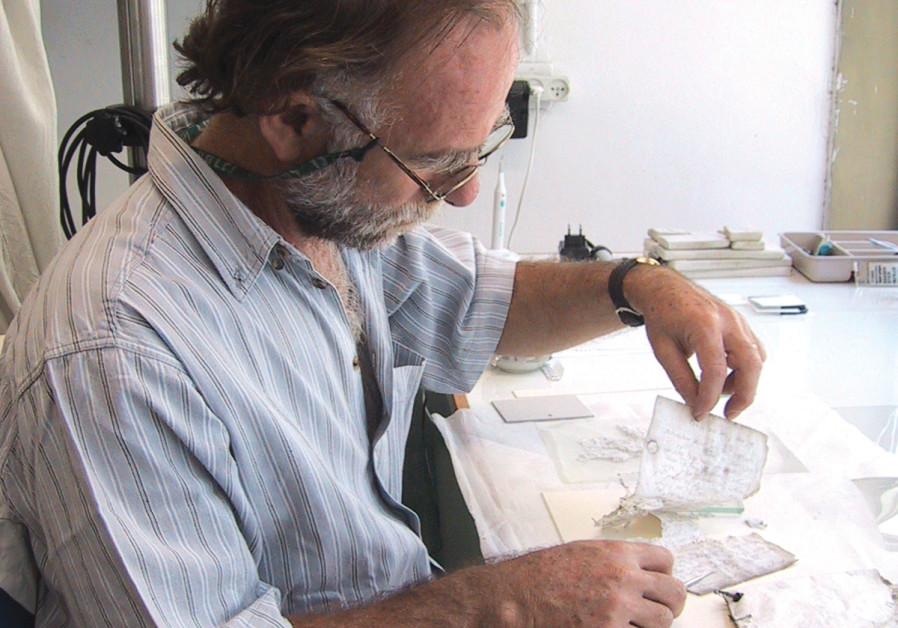 Michael Maggen separating the pages in the Israel Museum laboratory