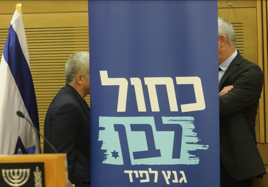 Blue and White leaders Benny Gantz (R) and Yair Lapid share words behind a party poster