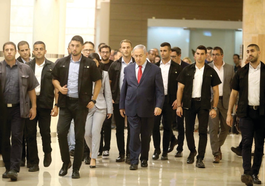 PRIME MINISTER Benjamin Netanyahu walks with his entourage in the Knesset on Wednesday night.