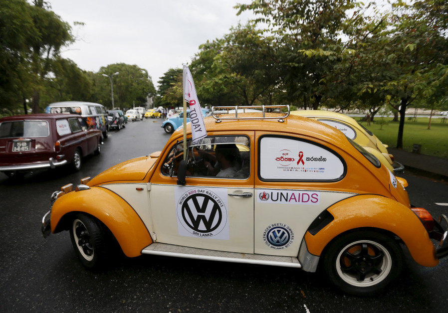 "Volkswagen beetle cars drive in a file during a ""World AIDS Day 2015"" rally"