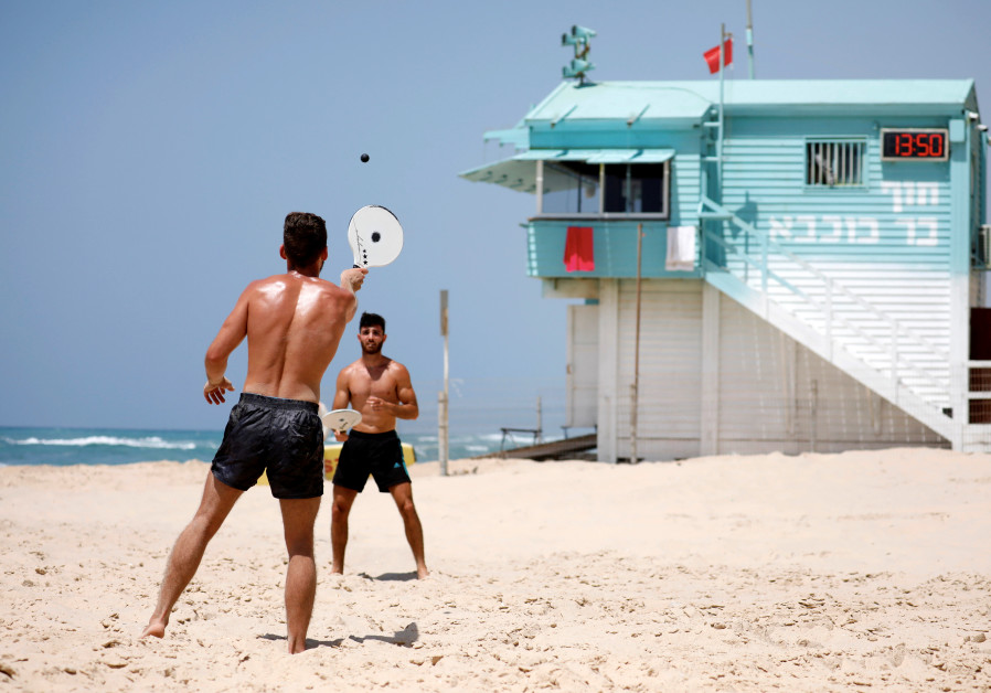 "People play paddle ball, known in Hebrew as ""matkot"", a popular Israeli sport, at a beach in Ashkelo"