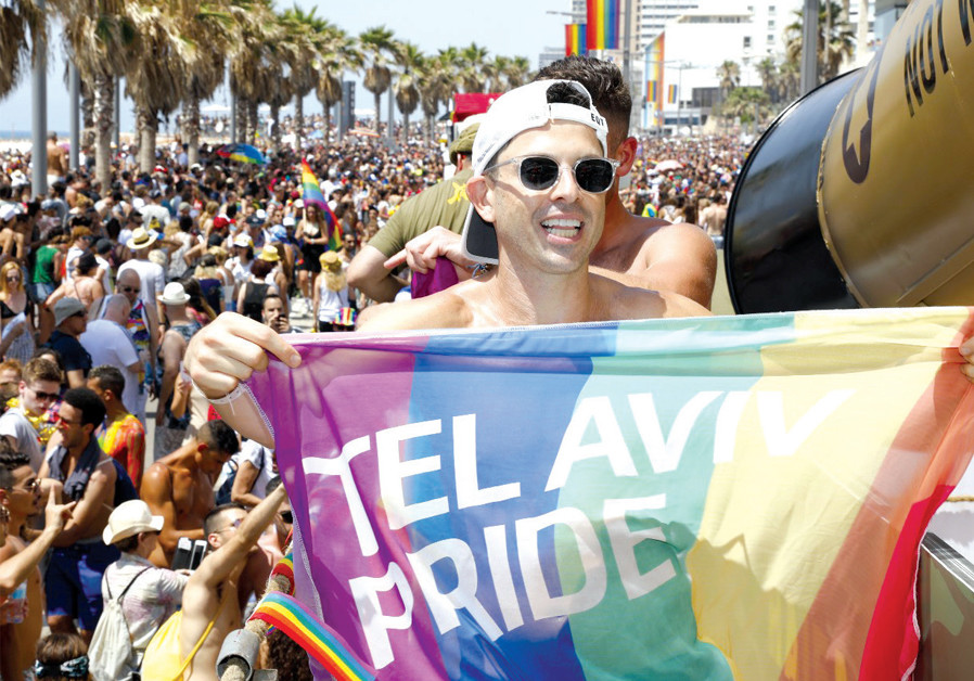 AGAINST THE backdrop of thousands, a 2018 Pride Parade attendee on a float shows off his Tel Aviv Pride flag. (Credit: ANAV SILVERMAN PERETZ)