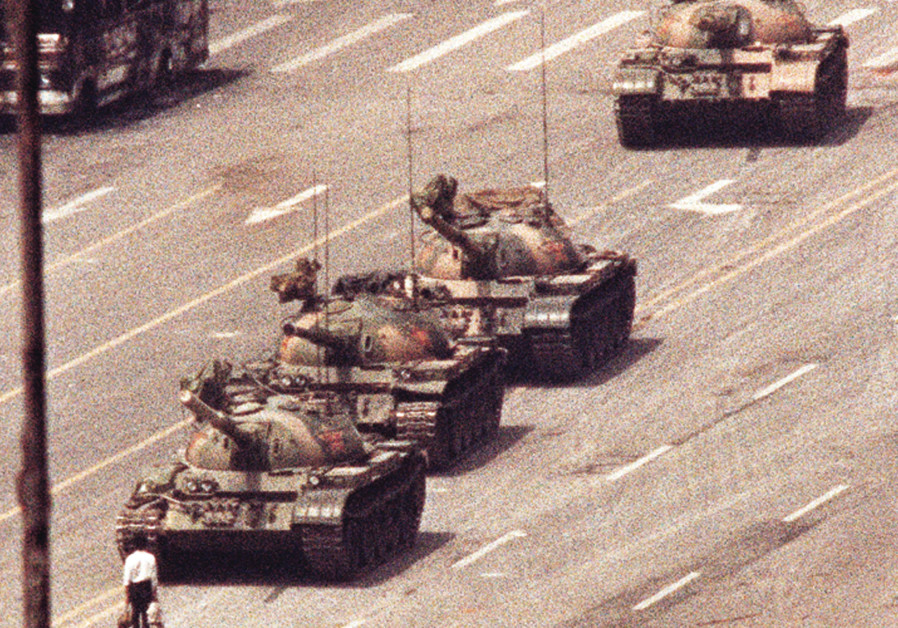 THE ICONIC PHOTO of a man standing in front of a convoy of tanks in the Avenue of Eternal Peace in B