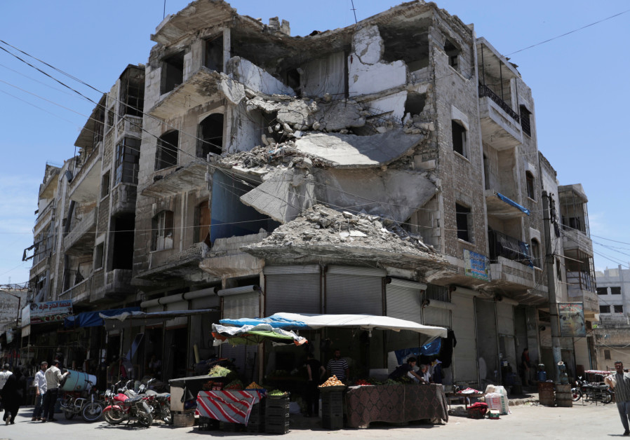 People walk past a damaged building in the city of Idlib on May 31, 2019.