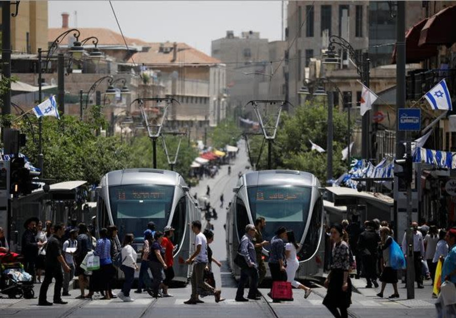 Pedestrians cross a street next to the light rail trams in Jerusalem May 11, 2017.