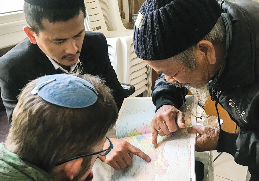 IN MIGDAL Ha'emek, writer Mishael Dickman (bottom left), assisted by translator Gavriel Lhungdim (top left), listen as Manipur native Elitzur Haokip points out his birthplace on the world map, as well as locations where he thinks other lost tribes dwell. (Credit: LAURA BEN-DAVID)