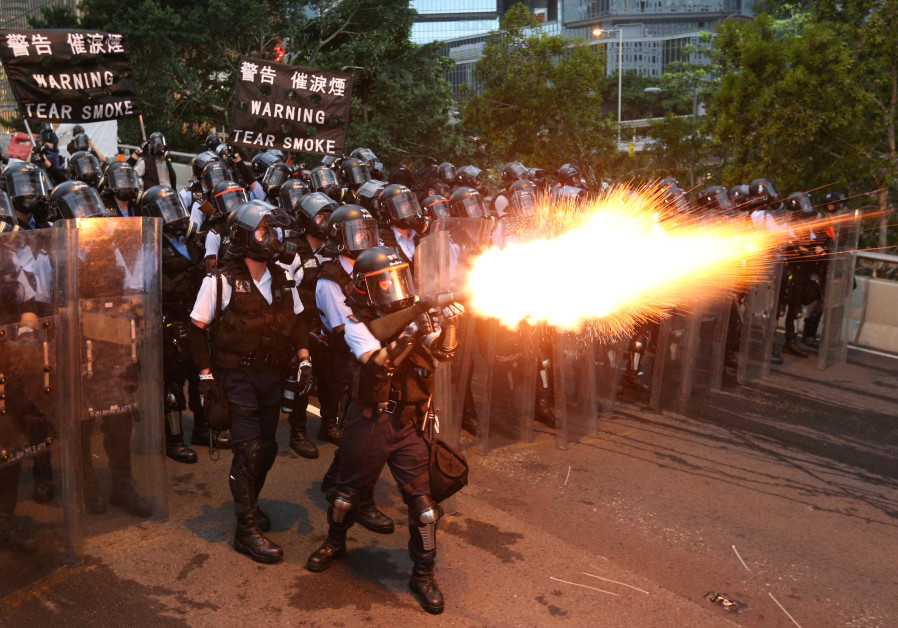 Police officers fire a tear gas during a demonstration against a proposed extradition bill in Hong K