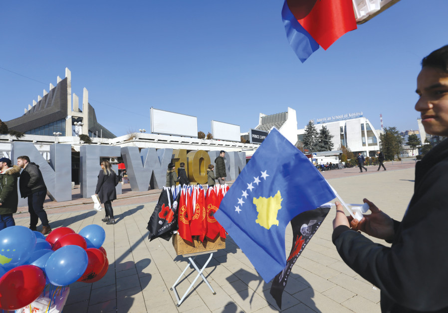 A MAN holds a Kosovo flag