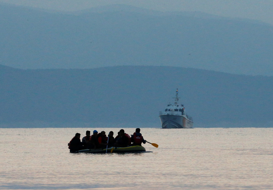 Migrants in a dinghy paddle their way on the Mediterranean Sea to attempt crossing to the Greek isla