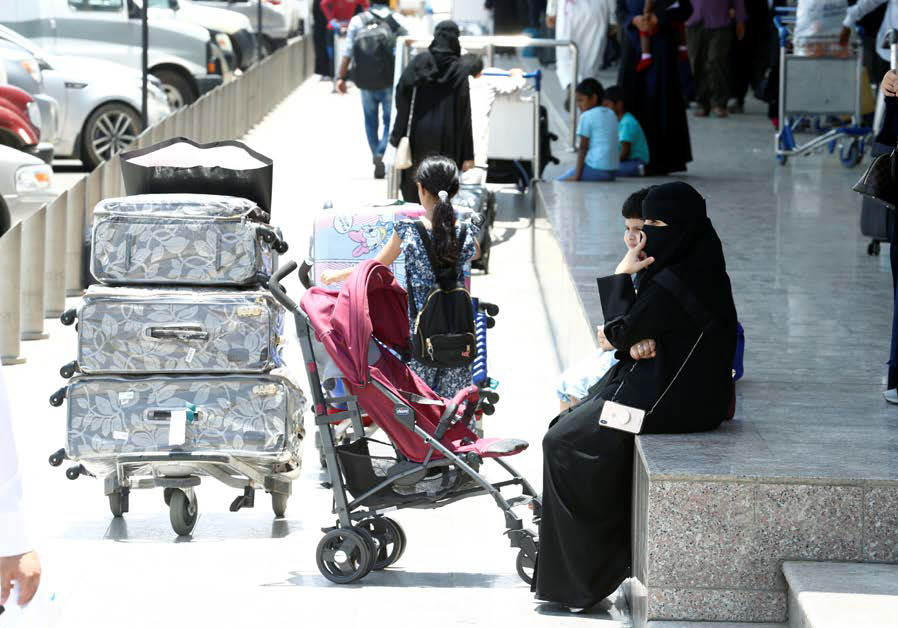 PASSENGERS ARE seen on June 13 outside Saudi Arabia's Abha International Airport after it was attacked by an area Houthi group. (Credit: FAISAL AL NASSER/ REUTERS)