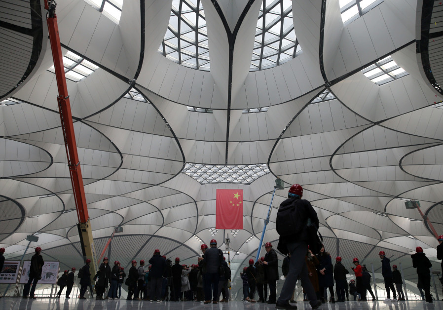 Visitors are seen under a Chinese flag at the terminal hall of the Beijing Daxing International Airport under construction, during a media tour on the outskirts of Beijing (Credit: China Daily via Reuters)