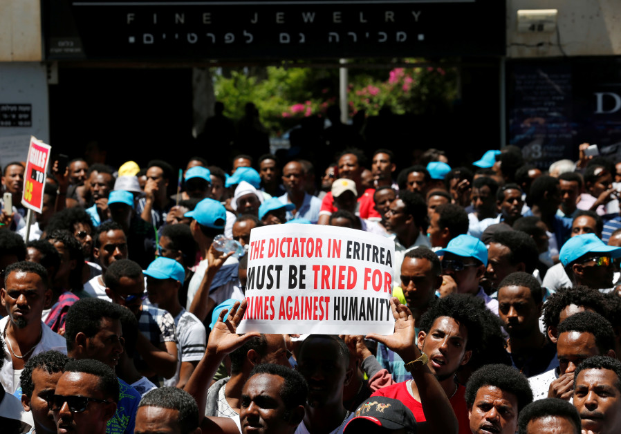 Eritrean refugees hold placards during a demonstration in support of a recent U.N. report that accus