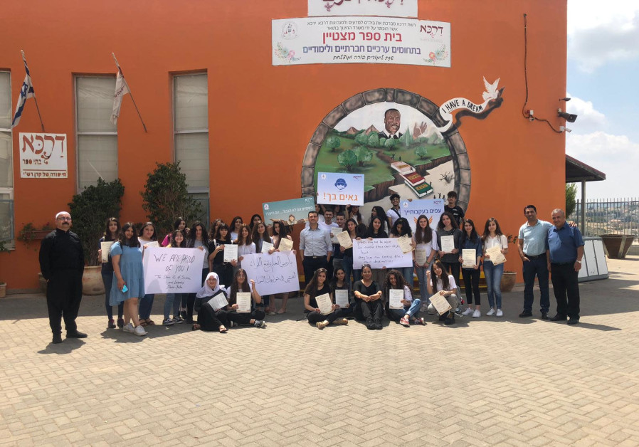 Students and staff of the school where G. graduated from in a picture congratulating him