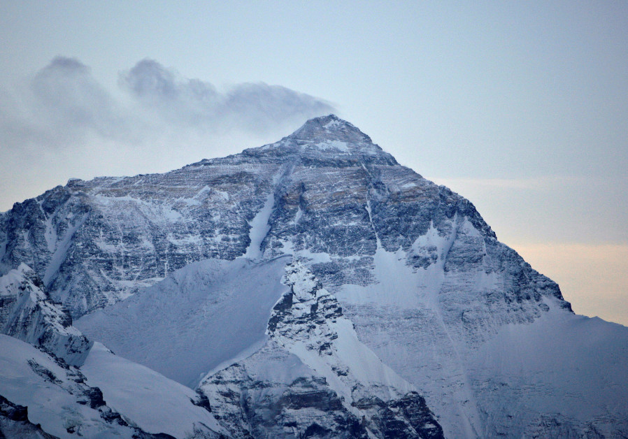 Wind blows snow off the summit at dusk of the world's highest mountain Mount Everest, also known as