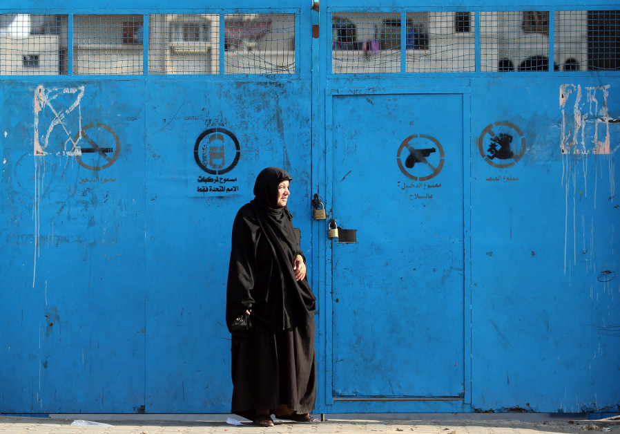 A Palestinian woman stands outside a closed school run by the United Nations Relief and Works Agency