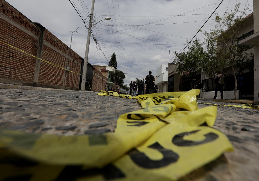 Yellow police tape lies on the road as federal agents work at a crime scene in the town in Mexico