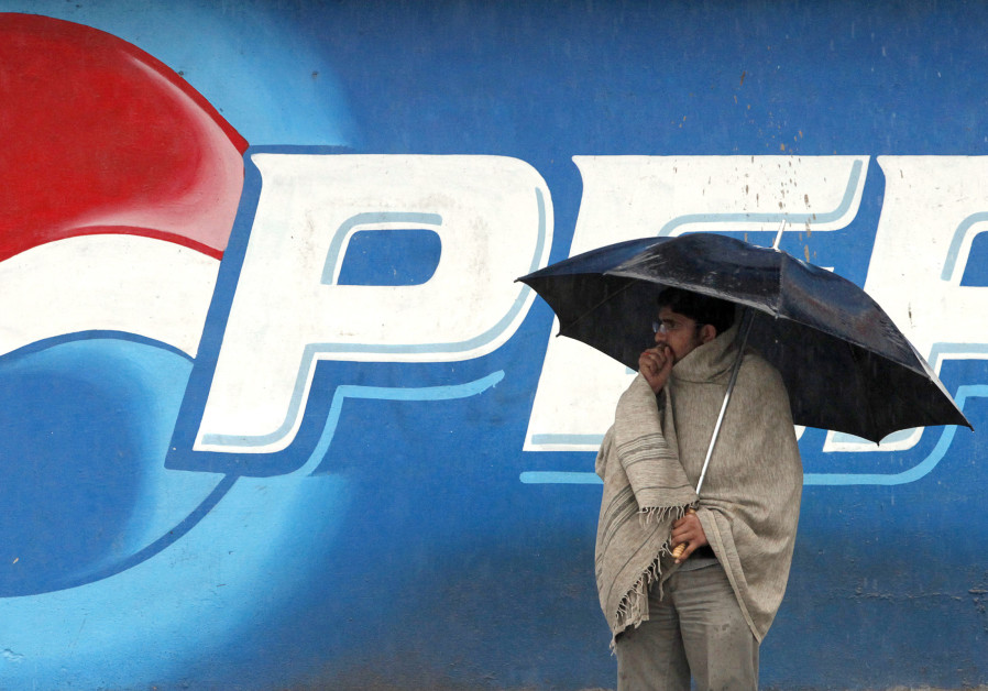 A man stands next to a Pepsi advertisement while using an umbrella in the rain, in Rawalpindi